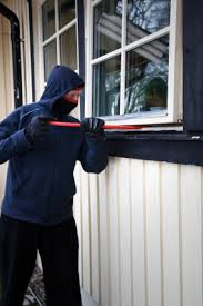 Masked intruder using a crowbar to break into a home through the first floor window