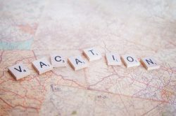 Scrabble pieces on world map spelling out vacation