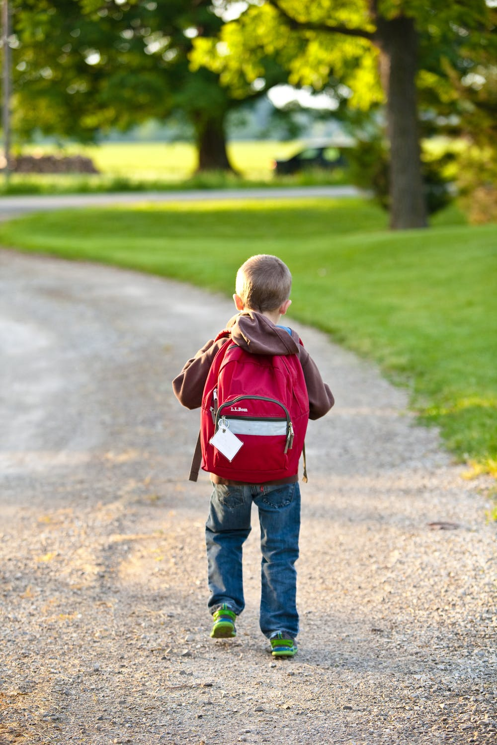 young child with red backpack walking home from school